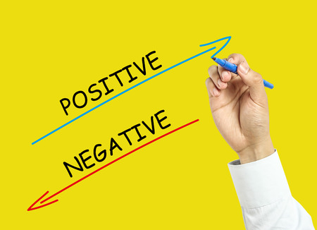 board marker: Businessman is drawing positive and negative concept with marker on transparent board with yellow background. Stock Photo