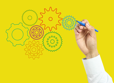 board marker: Businessman is drawing gears with marker on transparent board with yellow background.