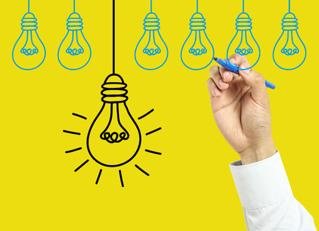 Businessman is drawing light bulbs with marker on transparent board with yellow background. photo