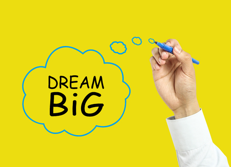 Businessman is drawing dream big concept with marker on transparent board with yellow background. photo
