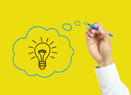 Businessman is drawing good idea concept with marker on transparent board with yellow background. photo