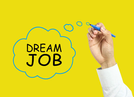 dream job: Businessman is drawing dream job concept with marker on transparent board with yellow background.