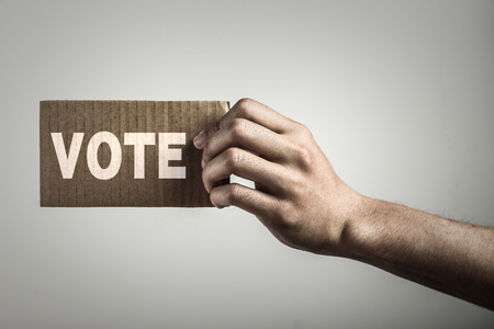 Hand with brown card is showing vote with gray background. photo