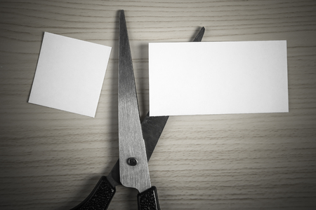 snip: White paper is cut into two pieces by scissor. Stock Photo