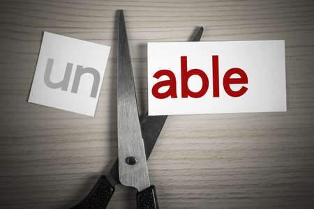 able: A scissor is cuting able from unable on the desk.