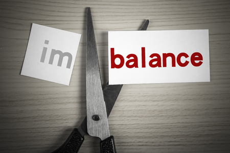 imbalance: A scissor is cuting balance from imbalance on the desk.
