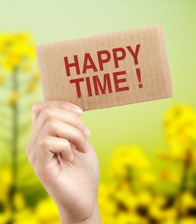 morphing: Happy time brown card is holden by woman hand with beautiful natural background. Stock Photo