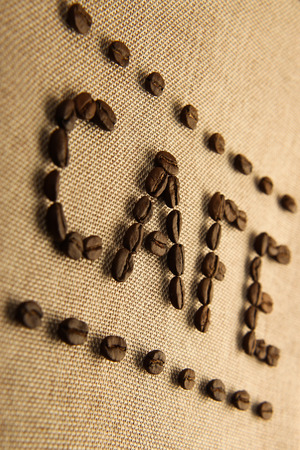 coffee sack: Roasted coffee beans making the word CAFE on the burlap background.