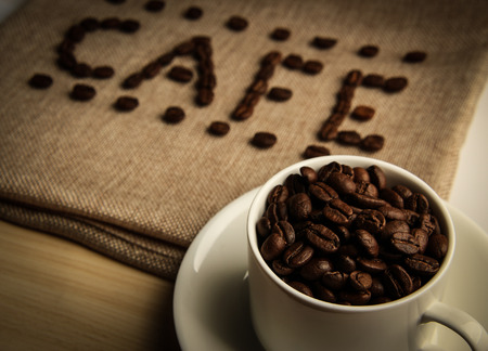 coffee sack: A cup of coffee beans with the word CAFE made by coffee beans on the burlap background. Stock Photo