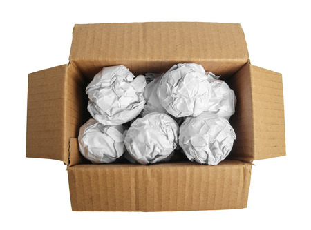 packing material: Paper balls are in the brown box on white background. Stock Photo