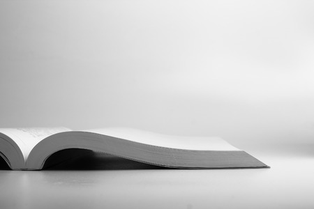 lifelong: An opened book laying on the blank white surface.