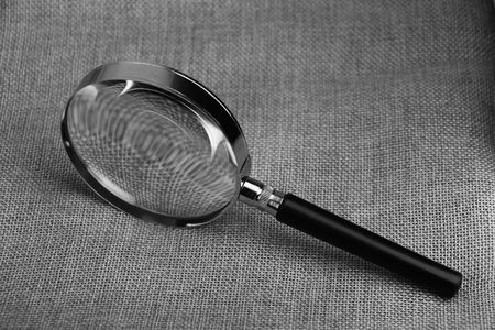 optical instrument: Magnifying glass is lying on the burlap sack.