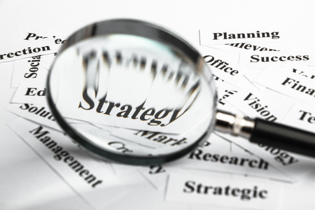 Magnifying glass is focusing on the strategy word with lot of other business concept words around. photo