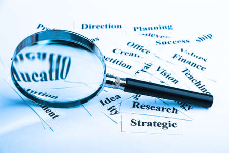 strategic focus: Magnifying glass and lot of other business concept words paper is showing the concept of business vision.