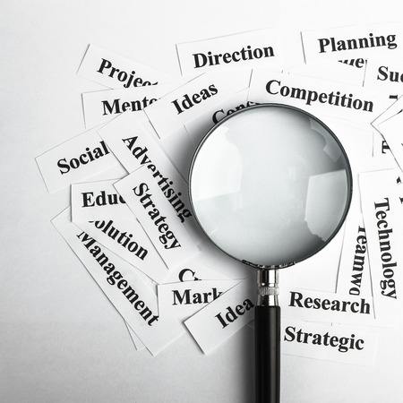 Magnifying glass and lot of other business concept words paper is showing the concept of business vision concept. Blank space of magnifying glass is for your edit. photo