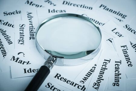 buzz word: Magnifying glass and lot of other business concept words paper is showing the concept of business vision concept. Blank space of magnifying glass is for your edit.