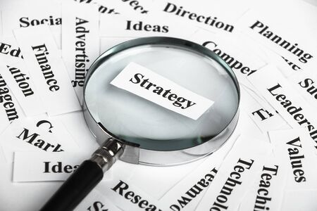 buzz word: Magnifying glass is focusing on the strategy word with lot of other business concept words around.