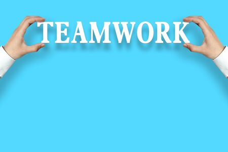 cohesion: Businessman is holding the Teamwork text against the blue background with copy space.