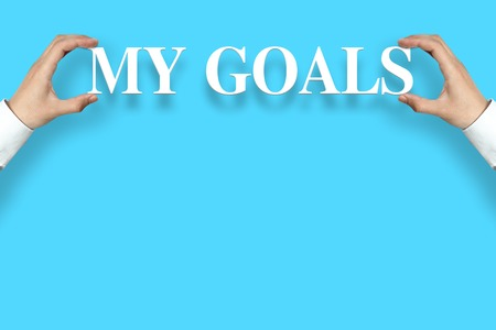 Businessman is holding the My Goals text against the blue background with copy space. Stock Photo