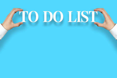 Businessman is holding the To do list text against the blue background with copy space. photo