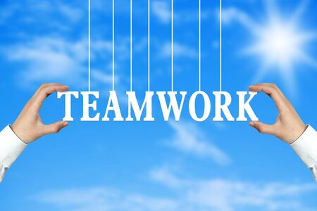 cohesion: Businessman is holding the Teamwork text against the blue sky background. Stock Photo