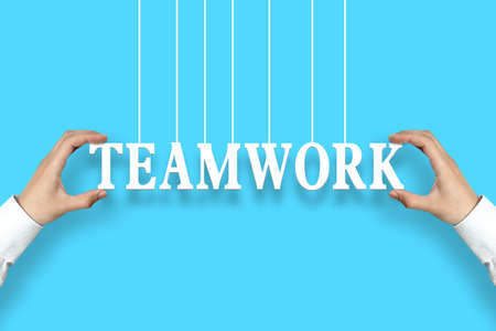 cohesion: Businessman is holding the Teamwork text against the blue background. Stock Photo