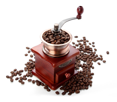 Some fresh coffee bean in coffee bean grinder is next to coffee bean isolated on white background. photo