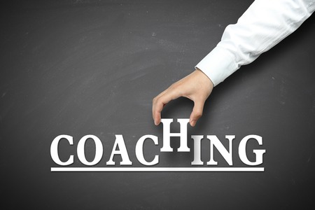 Coaching concept with businessman hand holding against blackboard background. Stock Photo