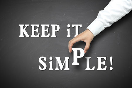 straightforward: Keep it simple concept with businessman hand holding against blackboard background.