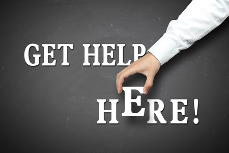 get help: Get help here concept with businessman hand holding against blackboard background.