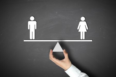 sex: Hombre es igual concepto femenino con el empresario mano sosteniendo contra el fondo de pizarra. Foto de archivo