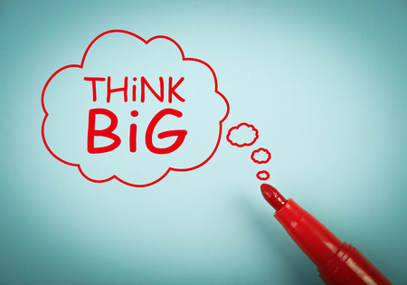 think big: Think big concept is on blue paper with a red marker aside. Stock Photo