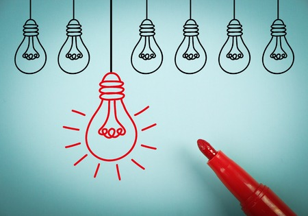 aside: Light Bulb idea concept is on blue paper with a red marker aside. Stock Photo