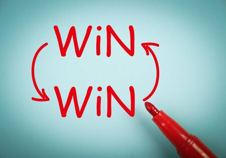 winning first: Win win concept is on blue paper with a red marker aside. Stock Photo