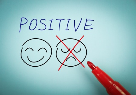 Positive thinking concept is on blue paper with a red marker aside. Stockfoto