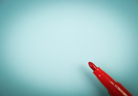 Blank blue paper background with a red marker on it.