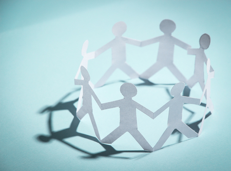 social care: Group of people made of paper are holding hands together. Team concept.