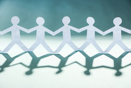 cohesion: Group of people made of paper are holding hands together. Team concept.