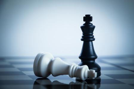 chess: Jaque mate ajedrez negro derrota al rey blanco en el tablero de ajedrez. Foto de archivo