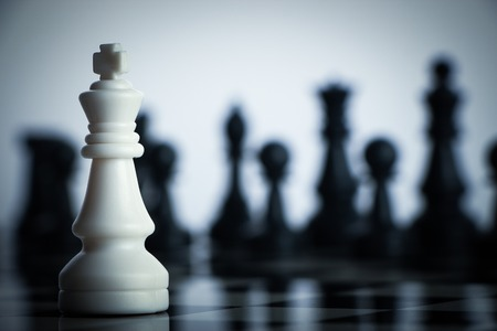 chess board: One chess is staying against full army of chess pieces. Stock Photo