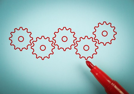 group solution: Gears is on blue paper with a red marker aside. Stock Photo