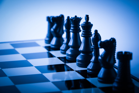 gradually: Chess pieces on board with gradually varied background. Strategy concept.