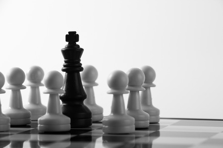 conversaciones: Rey negro está rodeado de blanco Piezas de ajedrez peón en un tablero de ajedrez. Foto de archivo