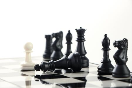 outwit: One pawn defeat the black army with the black king laying on the chess board. Stock Photo