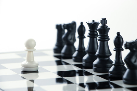 One pawn is staying against a lot of chess pieces.
