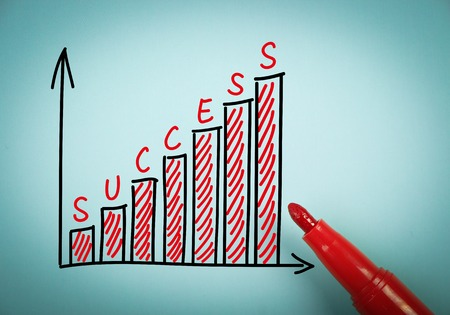 aside: Success graph is on blue paper with a red marker aside. Stock Photo