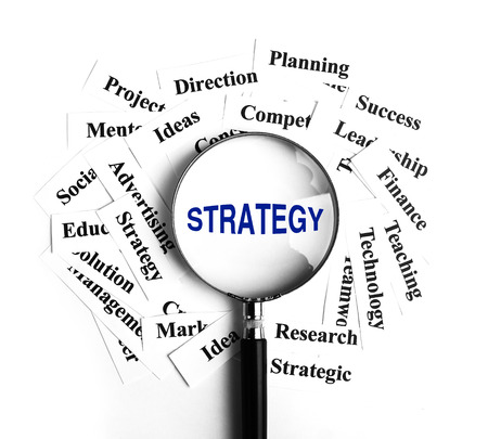 business it: Strategy magnifying glass with some business concept word paper around it.