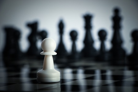 conflicts: One chess is staying against full army of chess pieces. Stock Photo