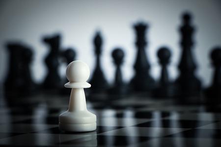 Uno de ajedrez se queda contra el ejército completo de piezas de ajedrez. Foto de archivo - 40373142
