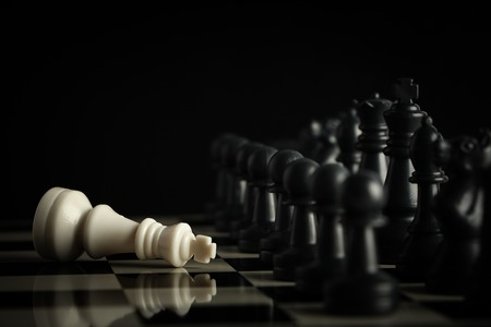 dark wood: Black chess army defeats white king on the chess board. Stock Photo